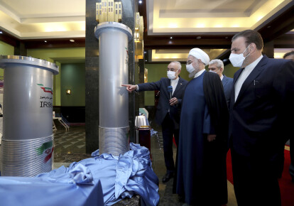 Президент Ирана Хасан Рухани (второй справа) слушает главу Организации по атомной энергии страны Али Акбара Салехи во время посещения выставки новых ядерных достижений Ирана в Тегеране, Иран, 10 апреля 2021 года