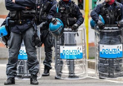 Офицеры полиции по борьбе с массовыми беспорядками стоят возле тюрьмы Сан-Витторе в Милане во время акции протеста заключенных,  в одной из карантинных красных зон Италии 9 марта 2020 г.