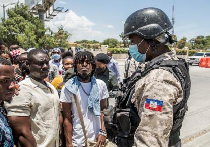 Полицейский наблюдает за тем, как граждане Гаити собираются перед посольством США в Табарре, Гаити, 10 июля 2021 г., прося убежища после убийства президента Жовенеля Моиза, объясняя это тем, что в стране слишком небезопасно и они опасаются за свою жизнь