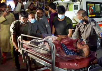 Волонтери та медичний персонал перевозять пораненого після двох потужних вибухів, за межами аеропорту в Кабулі 26 серпня 2021 р.
