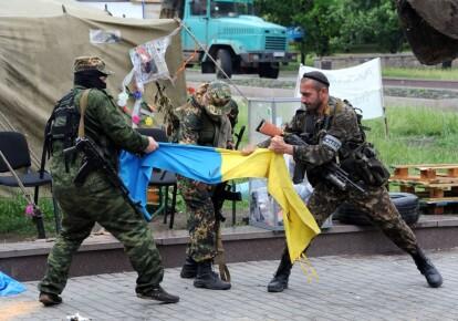 Боевики ДНР кромсают флаг Украины. Донецк, май 2014 г.