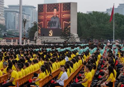Президент Китая и председатель Коммунистической партии Си Цзиньпин на экране, когда толпа слушает его речь на церемонии, посвященной 100-летию коммунистической партии на площади Тяньаньмэнь 1 июля 2021 г. в Пекине , Китай