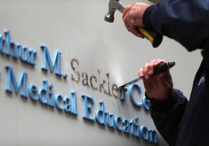 Рабочий убирает буквы фамилии Саклер с вывески в здании Университета Тафтса в Бостоне / Getty Images