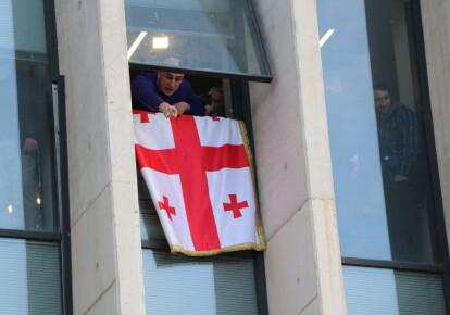 """Ника Мелиа, глава основного оппозиционного """"Единого национального движения"""" машет флагом, когда силы безопасности начинают операцию по его аресту"""