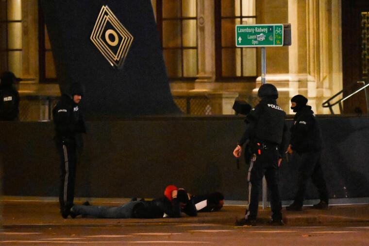 Австрийские полицейские обыскивают двух гражданских лиц перед Венской государственной оперой после стрельбы возле в Вене