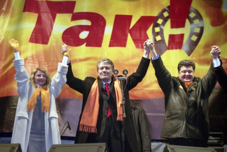 """Юлия Тимошенко, Виктор Ющенко и Петр Порошенко (""""Наша Украина"""") держатся за руки во время """"Помаранчевой революции"""" в декабре 2004 г."""
