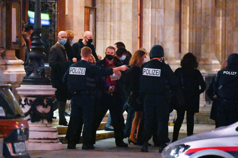 Австрийские полицейские охраняют посетителей, покидающих Венскую государственную оперу после стрельбы возле синагоги в Вене