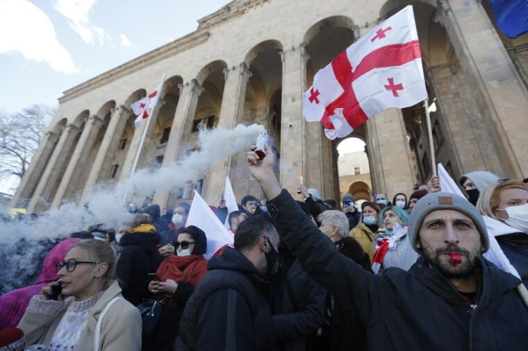 Люди принимают участие в митинге оппозиции в поддержку лидера грузинской оппозиции Ники Мелии перед зданием парламента в Тбилиси