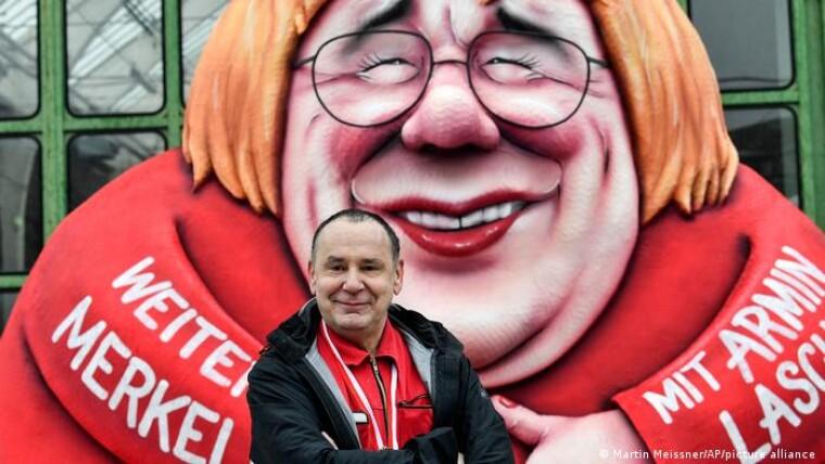Канцлер ФРГ Ангела Меркель предстала на карнавале в образе нового председателя партии ХДС и одного из вероятных кандидатов в канцлеры - Армина Лашета. Или наоборот. Лашет в образе Меркель. На переднем плане - легендарный автор сатирических повозок в Дюссельдорфе Жак Тилли