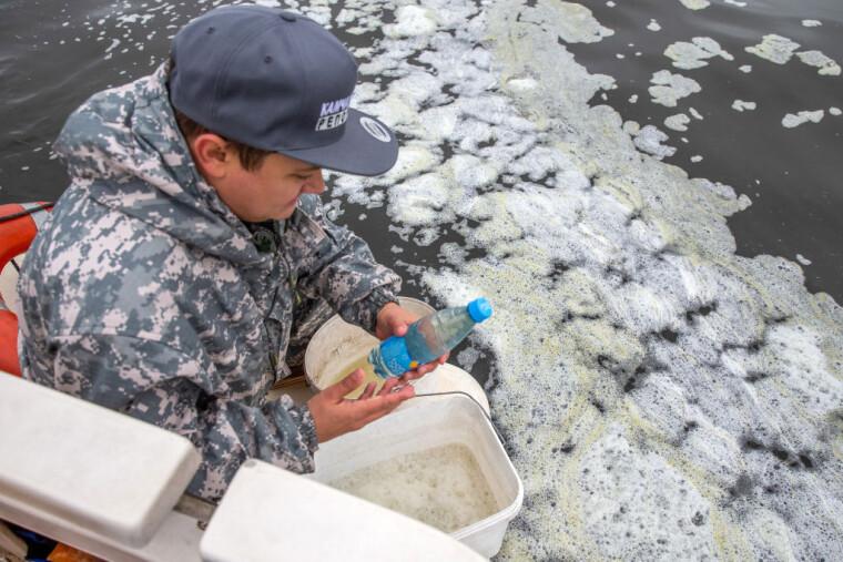 Чоловік збирає проби води з Авачинської губи у півострова Камчатка