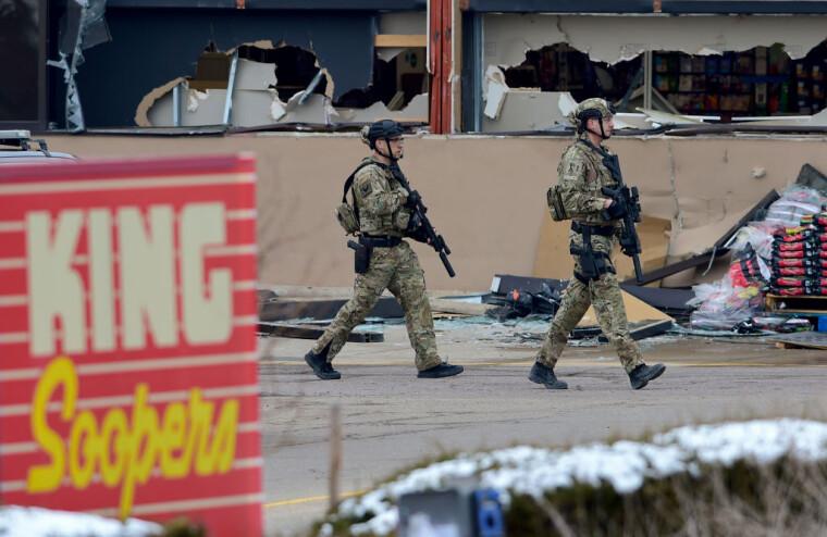 Вооруженные полицейские возле магазина, где неизвестный открыл стрельбу в Боулдере 22 марта 2021 г.