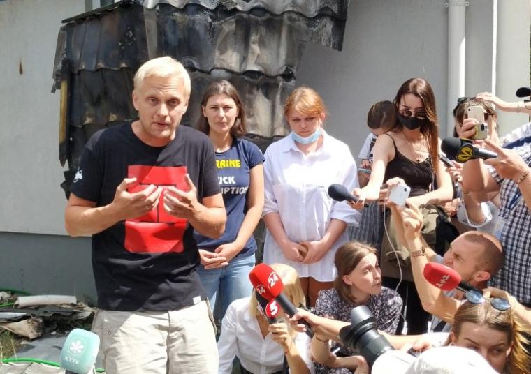 Виталий Шабунин отвечает на вопросы журналистов возле своего, поврежденного дома