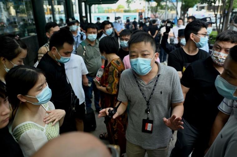 """Офицер полиции разговаривает с людьми, собравшимися в штаб-квартире Evergrande в Шеньчжене, 15 сентября 2021 года, поскольку китайский гигант недвижимости заявил, что столкнулся с """"беспрецедентными трудностями"""""""