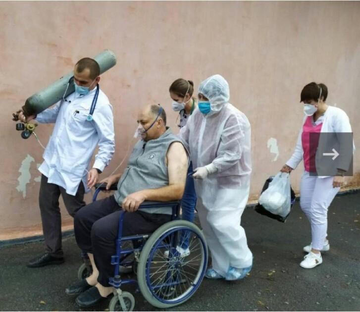 Медик несет тяжелый 10-литровый баллон для пациента, которого транспортируют на коляске